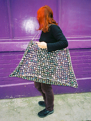 A woman carrying a huge handbag with pills woven into the fabric.