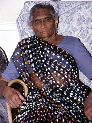 An elderly Indian woman wearing a sari containing many pills.