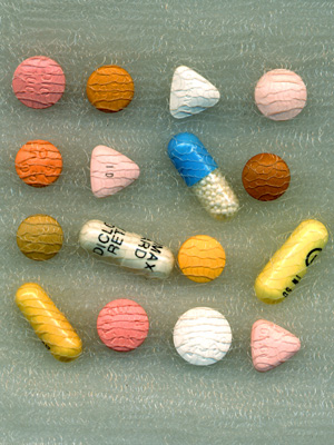 Sixteen pills, all different shapes, types and colours, in a piece of fabric.