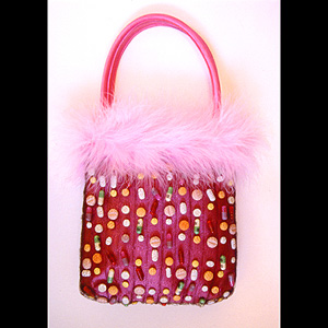A pink handbag, with pills covering the side.