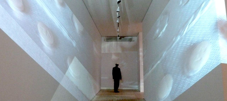 A man facing away at the end of a corridor with projected pills