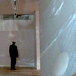 A man, facing away, at the end of a corridor