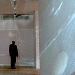 A man, facing away, at the end of a corridor