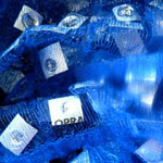 Detail of blue fabric containing pill packaging