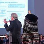 A man giving an exciting lecture next to a cape made of pills